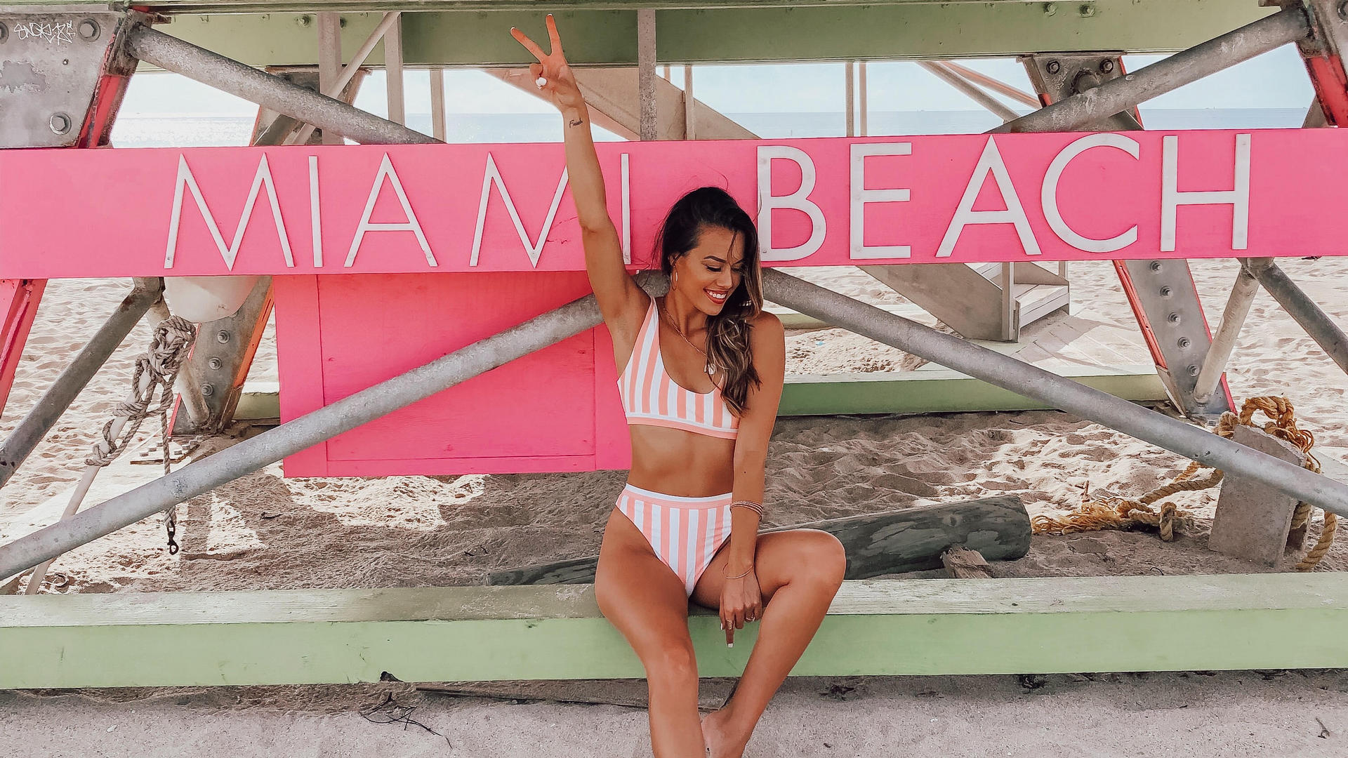 woman showing peace sign under miami beach sign